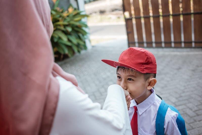 孩子震动和在学校前亲吻他的母亲的手 库存照片