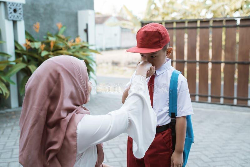 孩子震动和在学校前亲吻他的母亲的手 库存图片