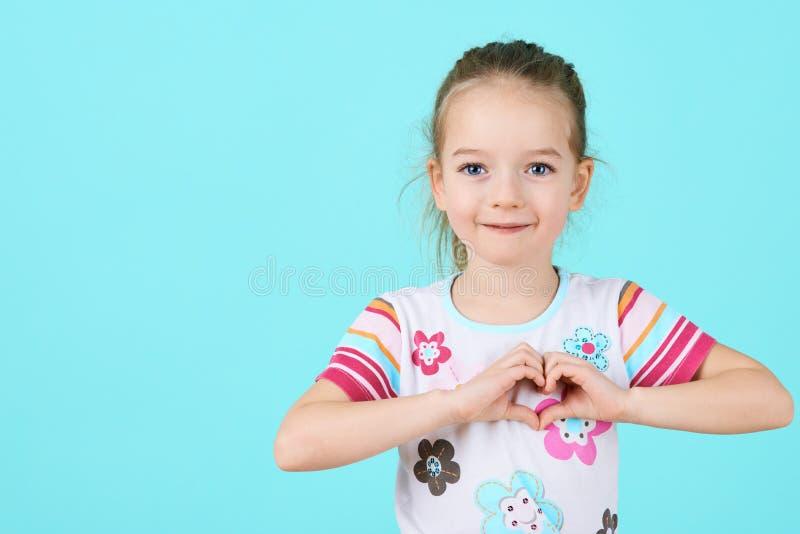 孩子,慈善,医疗保健,收养概念 做心脏形状姿态的微笑的小女孩 免版税库存图片
