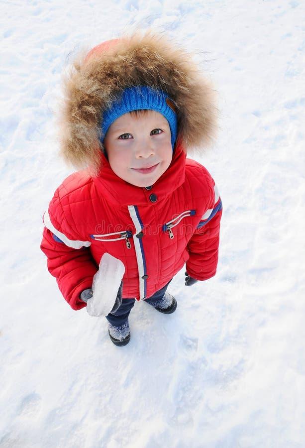 孩子,男孩拿着冰片断  冬天穿衣,夹克,帽子,手套 冬天背景的一个孩子 免版税库存图片