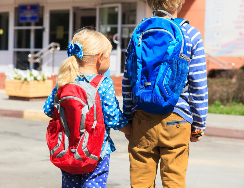 孩子去学校小男孩和女孩有背包的在街道上 库存图片