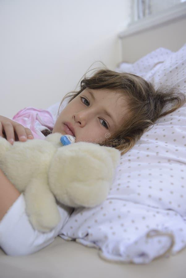 孩子以热病在床上 图库摄影