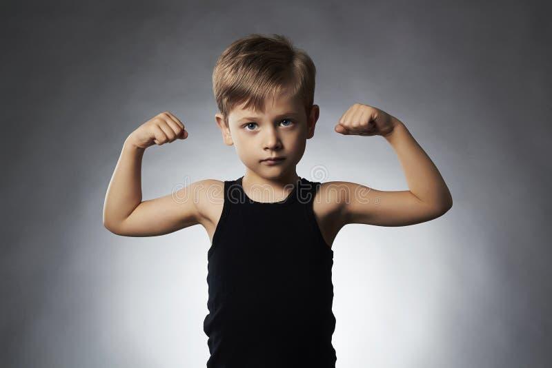 孩子 滑稽的男孩一点 炫耀显示他的手二头肌肌肉的英俊的男孩 免版税库存照片