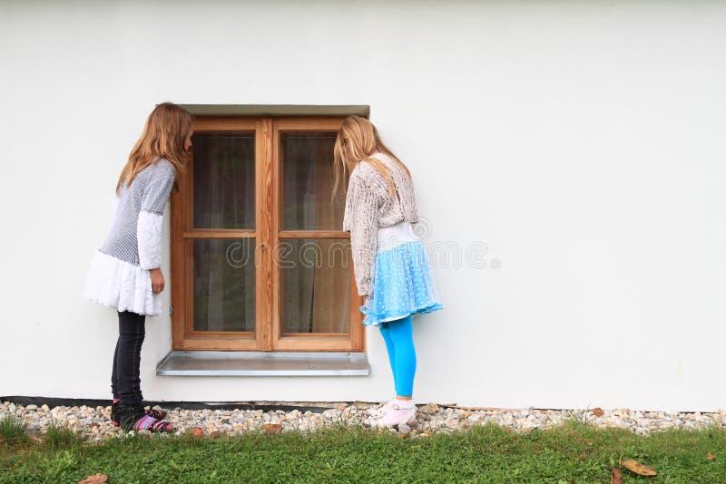 孩子-观看入窗口的女孩 免版税库存图片