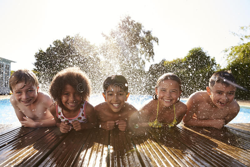 孩子画象获得乐趣在室外游泳池 库存照片