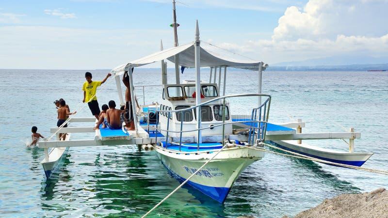 孩子临近渔夫的小船。 免版税图库摄影
