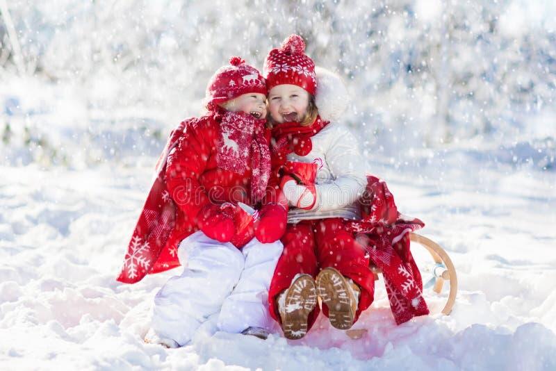 孩子sledding在冬天森林孩子喝在雪的热的可可粉 免版税库存照片