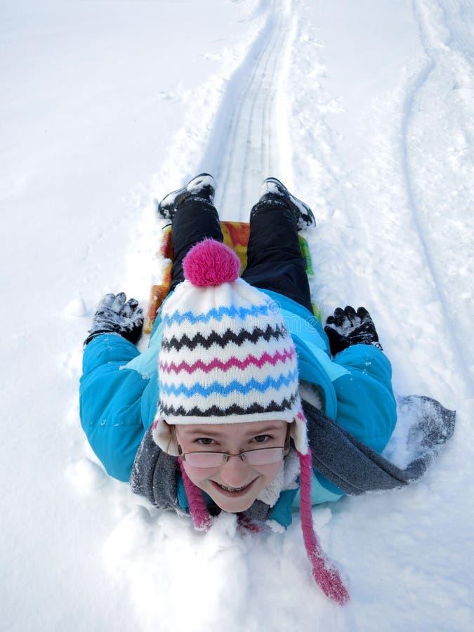 孩子Sledding在雪撬最快速度的雪小山下 库存图片