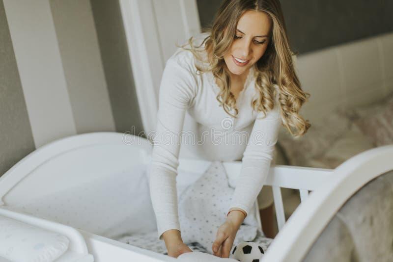 婴孩小儿床怀孕的安装妇女 图库摄影