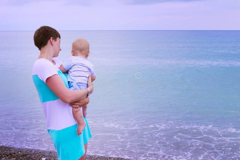 婴孩海滩母亲使用 查找海运 免版税库存照片