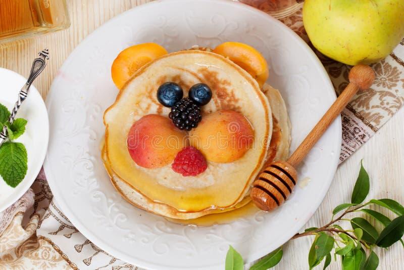 婴孩玩具熊草莓蓝莓和杏子,逗人喜爱的食物,蜂蜜的儿童的早餐薄煎饼微笑的面孔 免版税库存图片