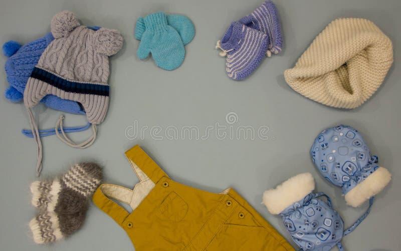 婴孩衣裳 平的位置儿童的衣物和辅助部件 温暖的冬天穿衣,手套,帽子,围巾 免版税库存图片