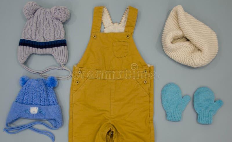 婴孩衣裳 平的位置儿童的衣物和辅助部件 温暖的冬天穿衣,手套,帽子,围巾 免版税库存照片