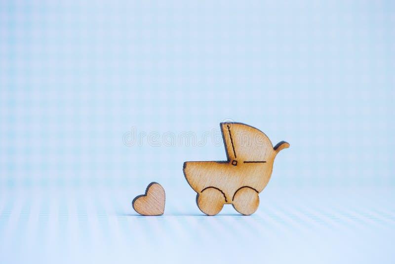 婴孩车和一点心脏木象在蓝色方格的bac 免版税库存照片