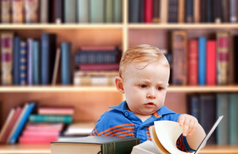 婴孩读书在图书馆里 免版税库存照片
