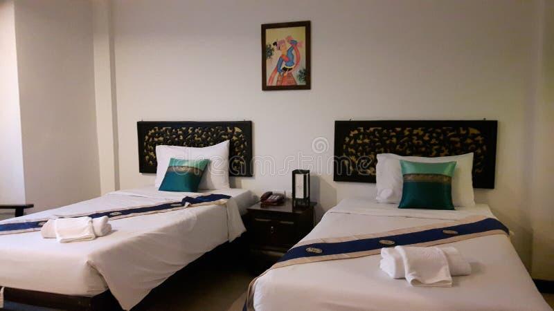 孪生供住宿的室 供住宿与白色卧具,装饰用枕头和蓝色床赛跑者 图库摄影