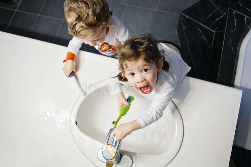 孪生特写镜头画象在刷有toothbrash的卫生间洗手间洗涤的面孔手上哄骗小孩男孩女孩牙 免版税图库摄影