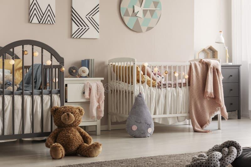 孪生的时髦的婴孩卧室与两个小儿床和女用连杉衬裤涉及地板 免版税库存照片