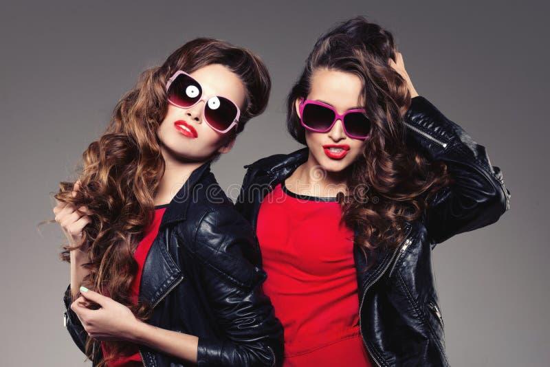 孪生笑两个时装模特儿的姐妹在行家太阳镜 库存照片