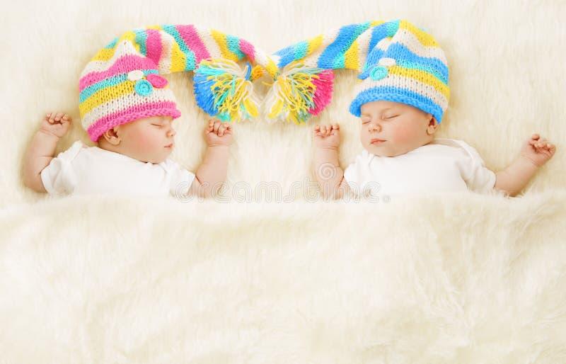 孪生婴孩睡眠帽子,睡觉新出生的孩子,逗人喜爱新出生 库存照片