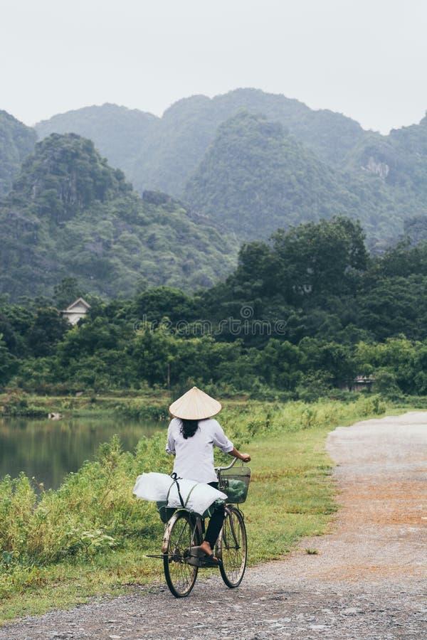 宁平市,越南- 2019年5月:米圆锥形帽子的越南妇女在Tam Coc国立公园骑自行车 库存照片