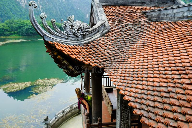宁平市/越南,08/11/2017:倾斜在有传统装饰瓦屋顶的佛教寺庙封入物外面的妇女在 免版税库存照片