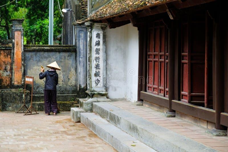 宁平市/越南,08/11/2017:有清扫传统佛教寺庙的地板在Tam的米帽子的地方越南妇女 免版税库存图片