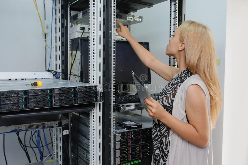 它与在服务器之间的片剂折磨的少妇工程师 免版税库存照片