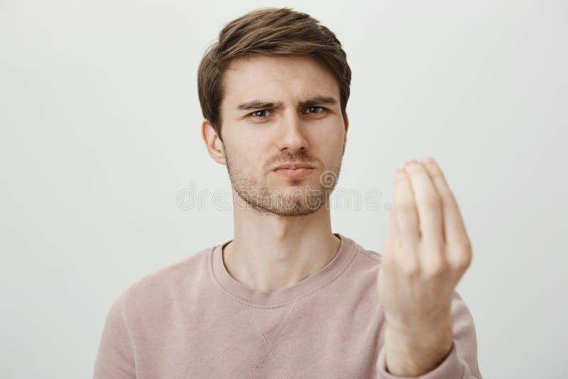 它是完善的展示 皱眉严肃的悦目成熟的男性斜眼看和,当做严密的面孔专家,显示时 免版税库存照片