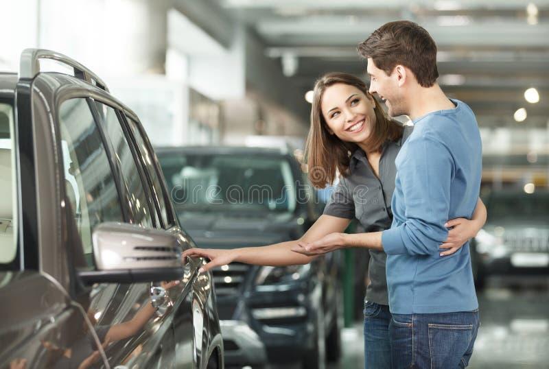 它是我要的这一辆汽车!站立在的美好的年轻夫妇 免版税库存照片