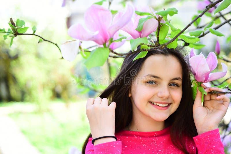 它的春天 逗人喜爱的女孩愉快微笑在春天风景 在开花的树附近的俏丽的女孩享用木兰开花 图库摄影
