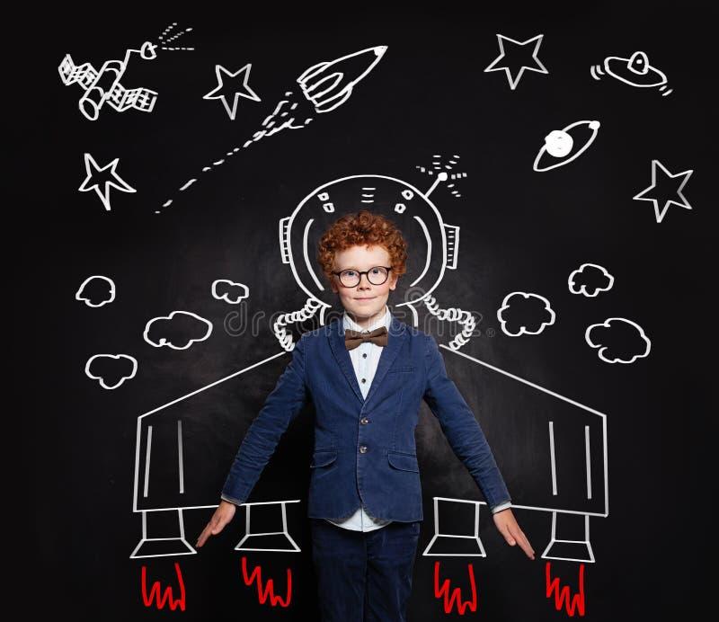 宇航员孩子 黑板背景的聪明的儿童男孩太空人与空间样式 免版税库存照片