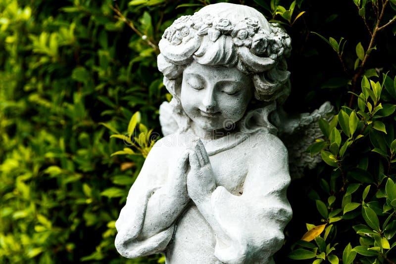 守护天使雕象在绿色庭院里 免版税库存照片