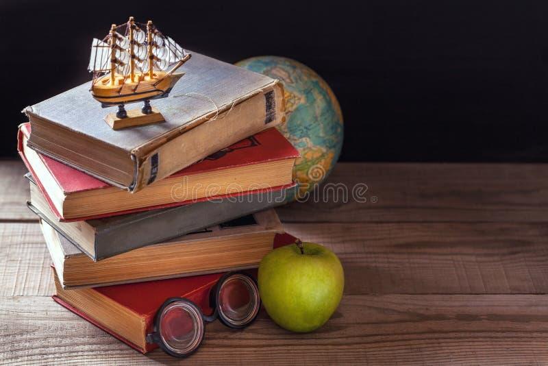 守旧派书、课本和学校用品在木桌上说谎 地球在背景中 免版税库存图片