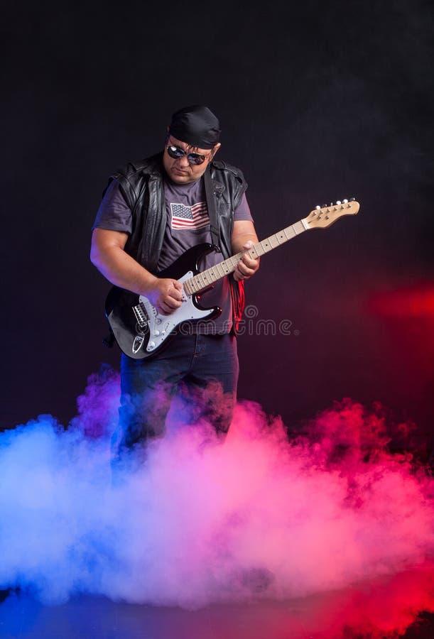 守旧派岩石音乐家弹吉他。 免版税库存图片