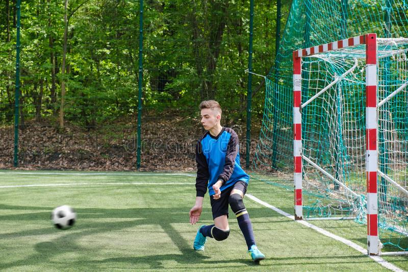 守门员拿到球 体育场守门员体育打地面猎物,草足球老板人,outdoorsc ompetition 图库摄影