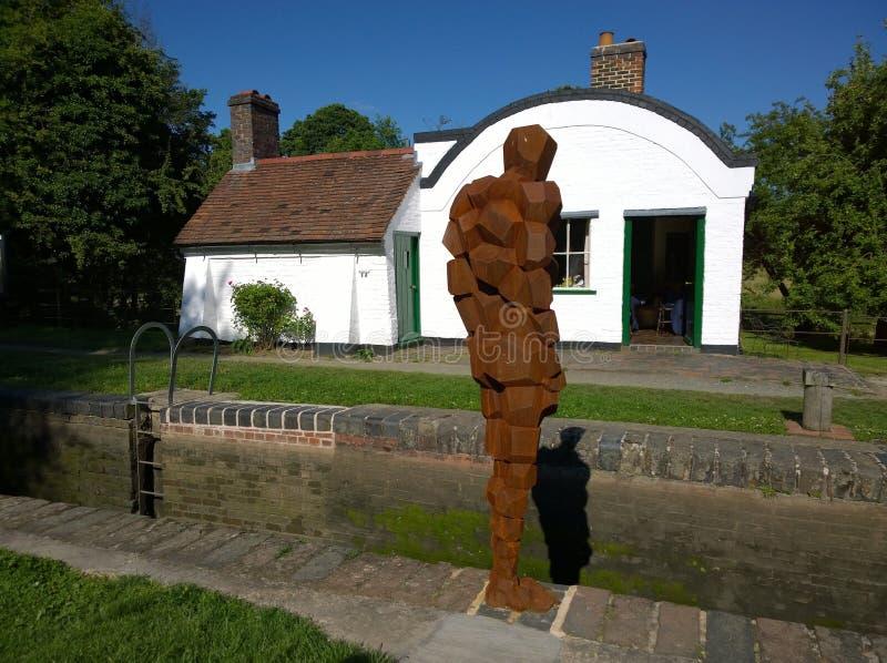 安东尼Gormley雕塑和水闸看管员房子 免版税库存照片