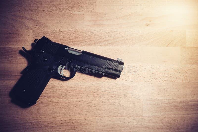 安全和安全概念:在一张木桌上的黑枪 免版税库存图片