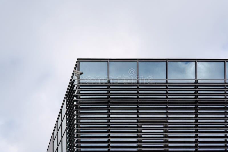 安全在现代玻璃和钢大厦,文本的阴暗天空空间的屋顶角落的CCTV照相机在背景中 库存图片