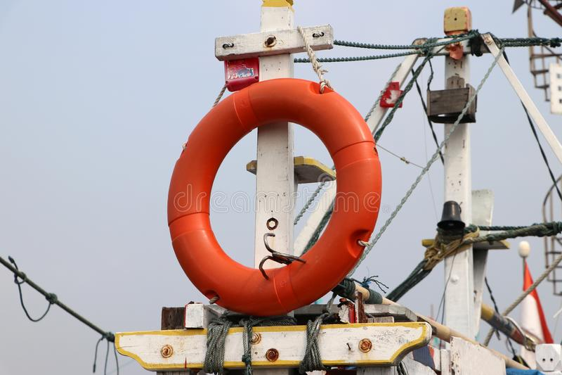 安全垂悬在渔船帆柱的救生圈 库存图片