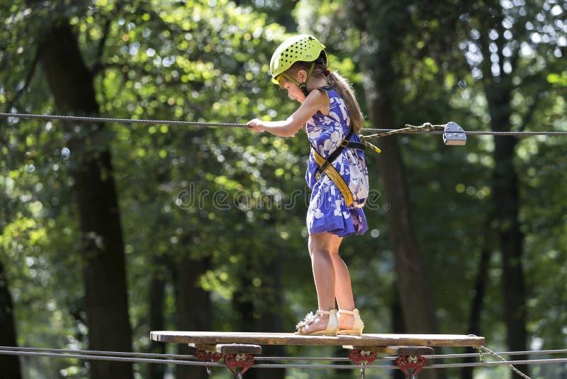 安全带的小孩子女孩和盔甲附有与马枪缚住在绳索途中在公园 库存图片