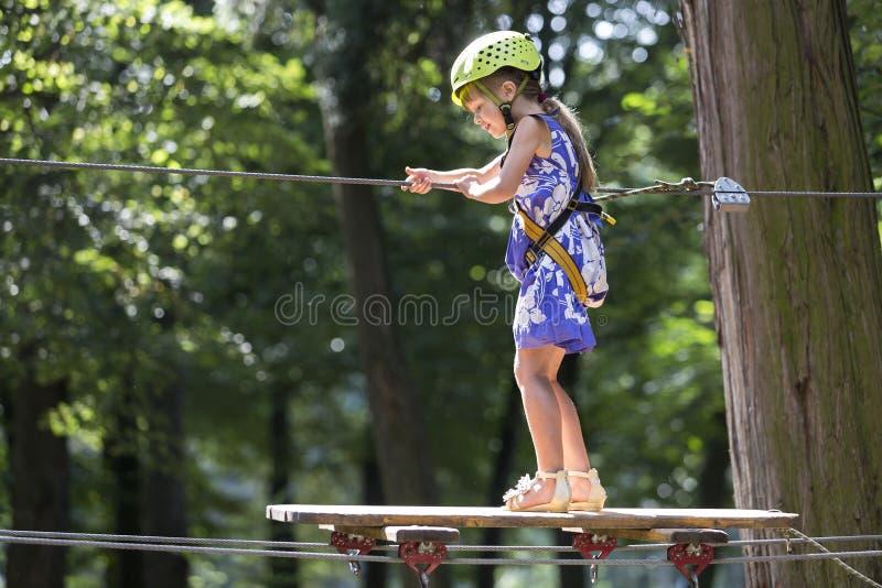 安全带的年轻微笑的女孩和盔甲附有与马枪沿绳索方式小心地缚住移动在休闲公园 库存图片