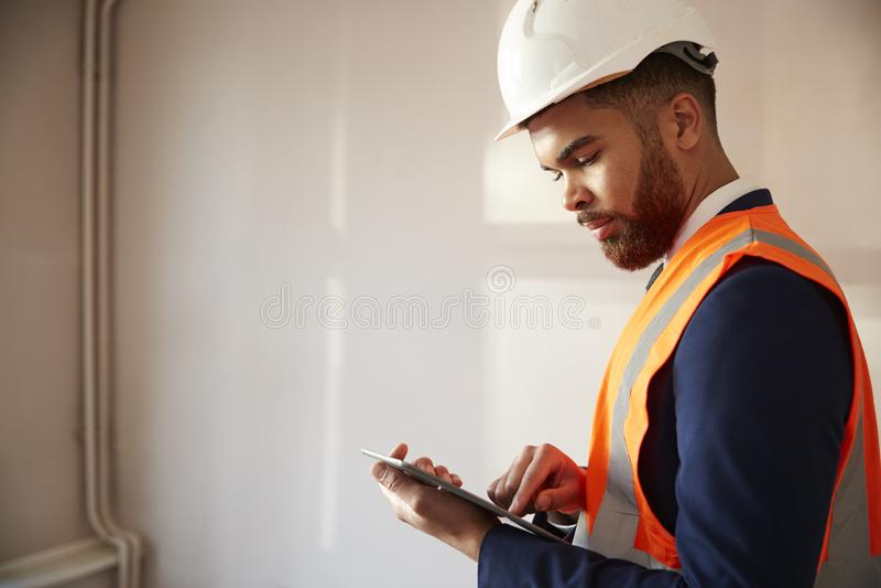 安全帽和高可见性夹克的测量员有数字片剂执行的议院检查的 库存照片