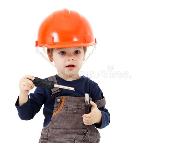 安全帽的小安装工有钳子和螺丝刀的在白色 免版税库存照片