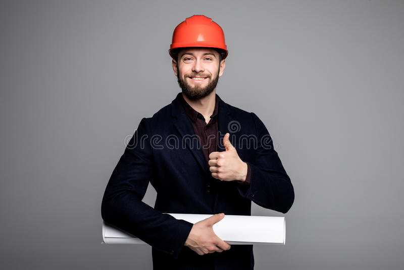 安全帽的有图纸的打手势在灰色的一位微笑的建筑师的画象赞许 免版税图库摄影