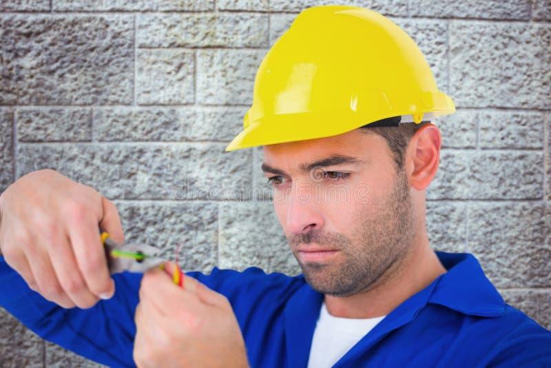 戴安全帽的电工的综合图象,当切开导线时 免版税库存图片