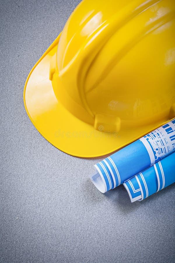 安全帽蓝色滚动了图纸在灰色背景constructi 库存图片