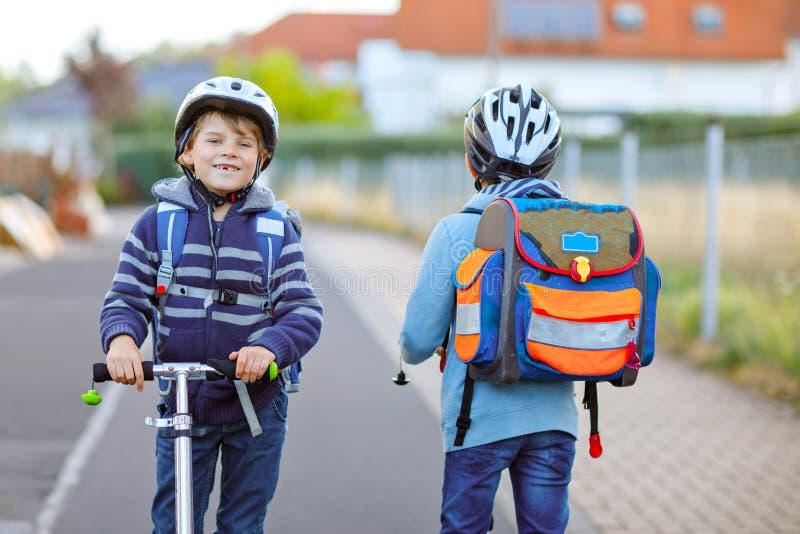 安全帽骑马的两个学校孩子男孩与滑行车在有背包的城市在好日子 愉快的孩子  库存图片