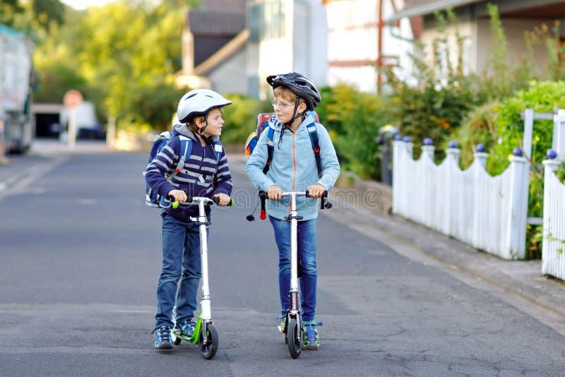 安全帽骑马的两个学校孩子男孩与滑行车在有背包的城市在晴天 愉快的孩子  库存照片