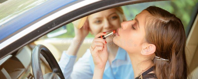 安全开车 应用在嘴唇的俏丽的妇女红色口红 有完善的构成的年轻女人在车轮 礼服方式金黄设计 图库摄影